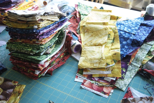 Round one: slice off a 4' tall strip across the longest edge of each piece of fabric. Stack similar colors together and prepare for dissection.