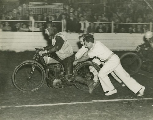 Motor bike racer getting a push start at the track, Brisbane | by State Library of Queensland, Australia