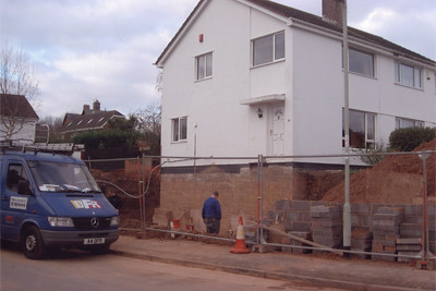 <p>Underpinned gable elevation of house to build basement. Tanked the walls with hot bitumen and built up two more storeys with substantial brick retaining walls and a patio.</p>