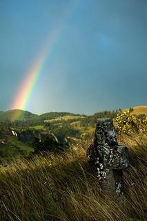 Stone cross overlooking huge rainbow