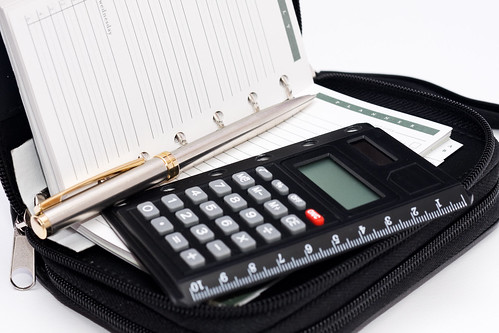 Calculator, pen and agenda in black organizer case | by Horia Varlan