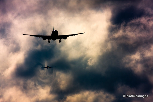 Commercial airplanes descending through clouds few miles from landing. London Heathrow Airport UK