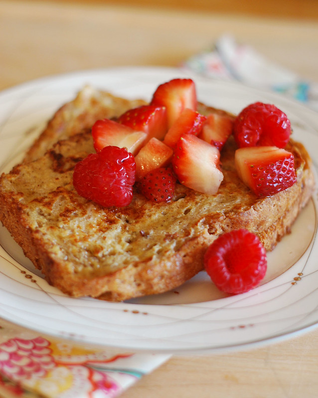 French toast made with homemade wheat oat bread and topped with fresh strawberries on a white plate