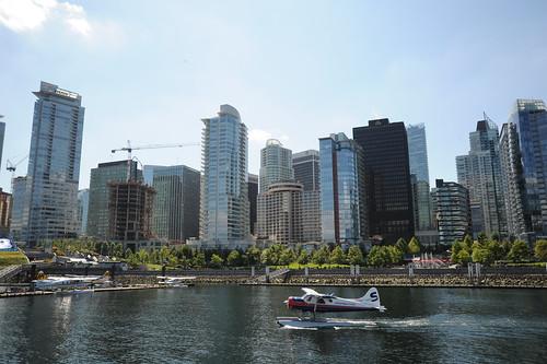 Float plane landing in Vancouver BC harbor, modern skyscrapers, cranes building, Life Release Project, Lotus Speech Canada | by Wonderlane
