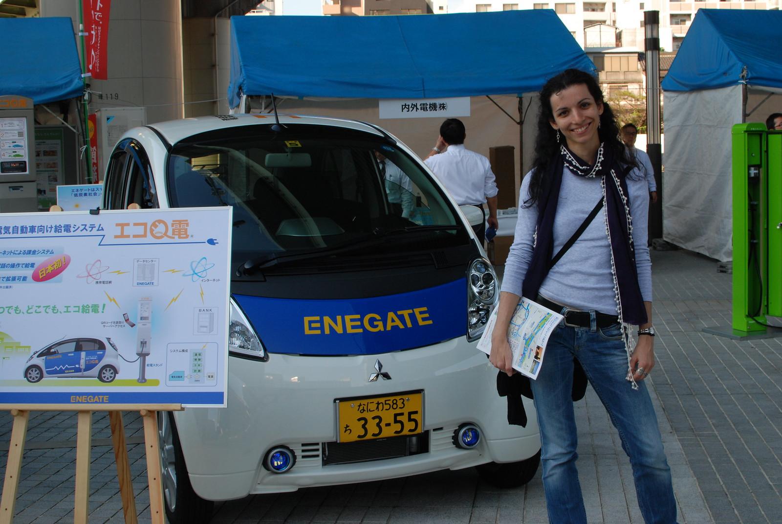 Angela delante de un coche eléctrico en una muestra en Osaka