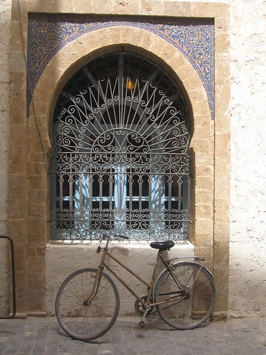 Arched window and Gazelle bike, Essaouira   by Mary Loosemore
