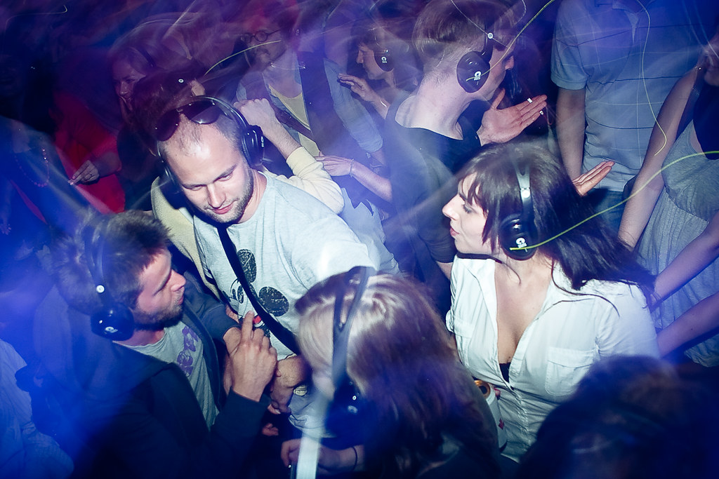 Image of a group of men and women wearing headphones in a silent disco