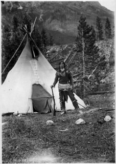 Man with a rifle in front of a teepee, Banff National Park, Alberta / Un homme tient un fusil devant un tipi au parc national Banff, en Alberta