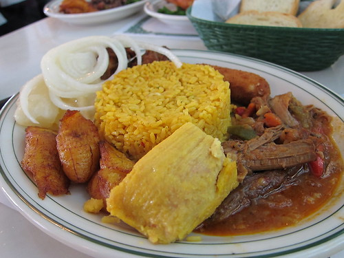 Full plate of Cuban food with rice, onions, meat, and sauces