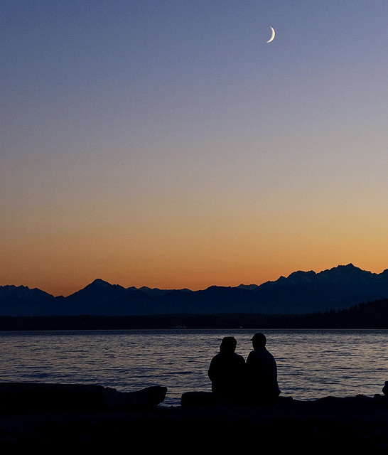 Beach couple + crescent moon over Olympics & Puget Sound