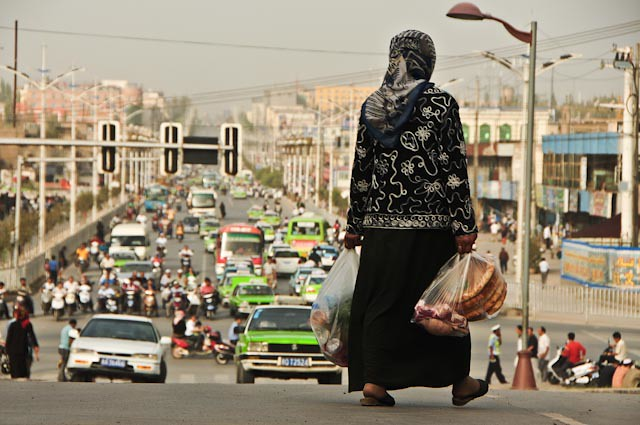 Woman crossing road in Asia