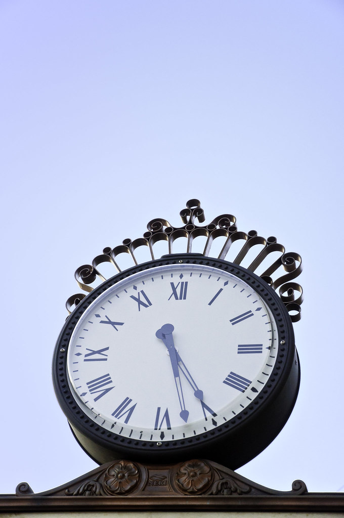 Ornate outdoor clock against blue evening sky