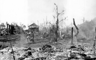 Natives leave smoldering wreckage of Dulag Village, Leyte, Philippines, Oct. 29, 1944   by J. Tewell