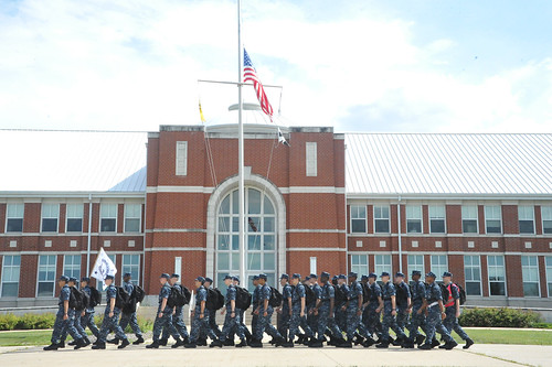 A recruit division marches past the American flag at half-mast. | by Official U.S. Navy Imagery