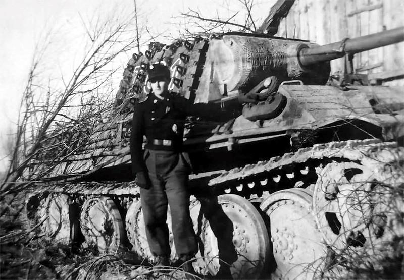 Un membre de l'équipage de la 3e division de panzer SS Totenkopf se tient à côté de son panzer v