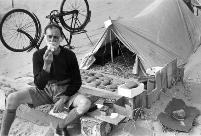 Kampeerder scheert zich / Camper shaving in front of his tent