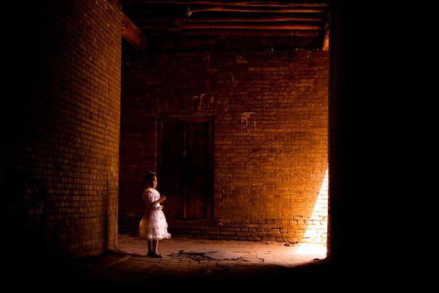 Little girl in big maze of Kashgar alleys