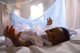 Infant surrounded by protective malaria bed net | by World Bank Photo Collection