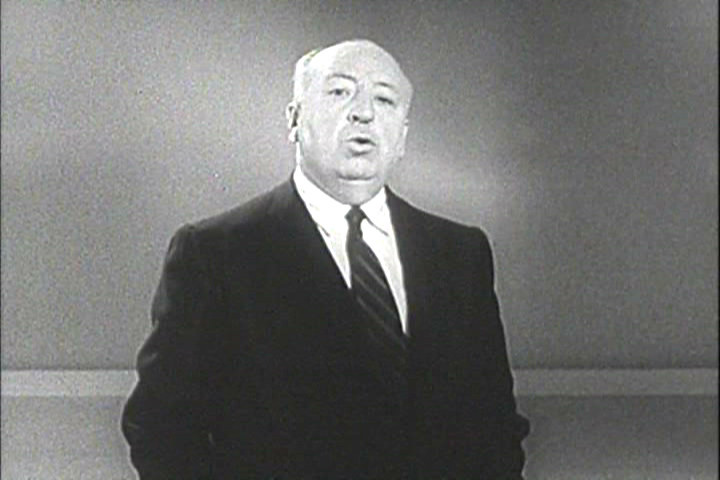 Alfred Hitchock, in suit and tie, facing and speaking to the camera.