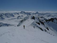 Po nejtěžším stoupání následuje plochý hřeben. Za lyžaři mohutná hora Flüela Wisshorn.
