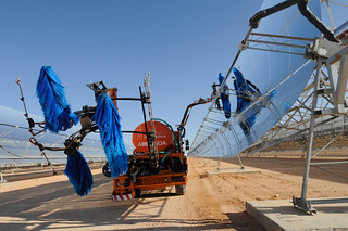 Solar panels being cleaned | by World Bank Photo Collection