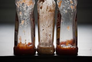 nearly empty sauce bottles | by Steve A Johnson