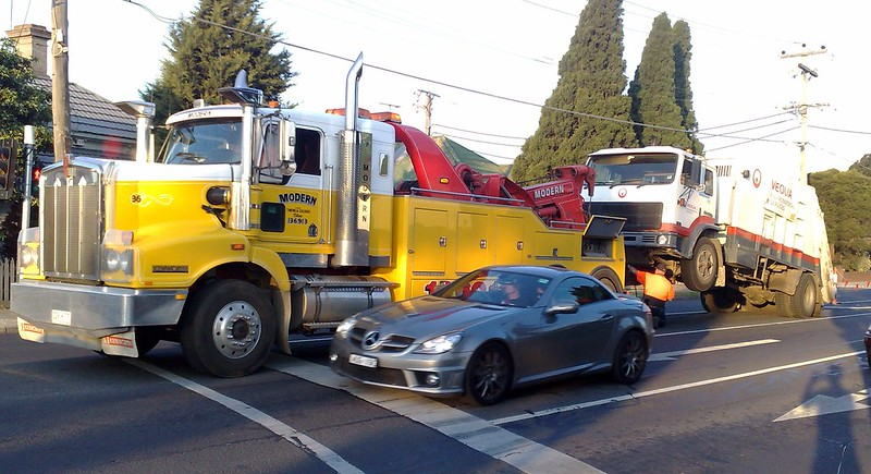 Tow truck towing a Veolia garbage truck