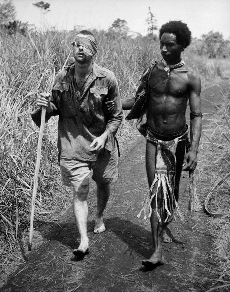 Blinded Australian soldier being helped to an aid station by a Papuan native along a road away from the Buna battlefront, by George Silk 1942