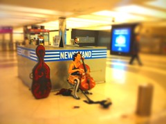 Unwoman playing cello in Montgomery BART station pswed TiltShift Generator