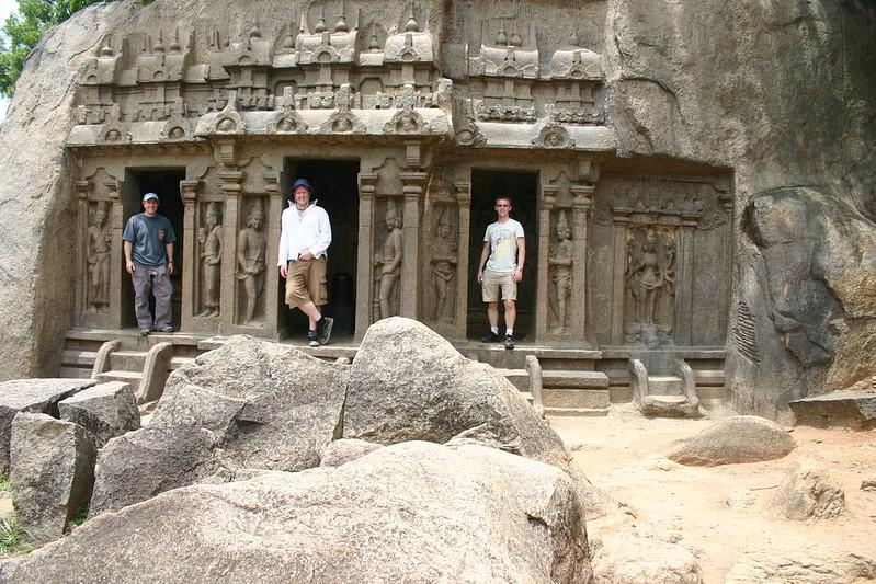 Three males stand in entranceways to a temple dedicated to Vishnu in Mahabalipuram.