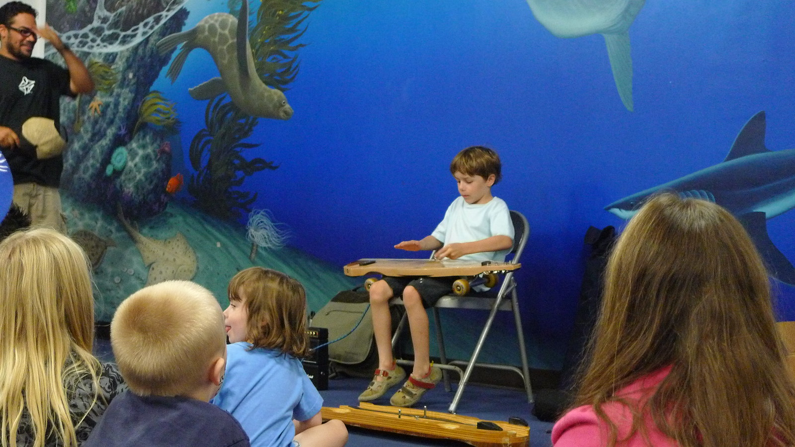 Aquarium guests try playing the skateboard guitar