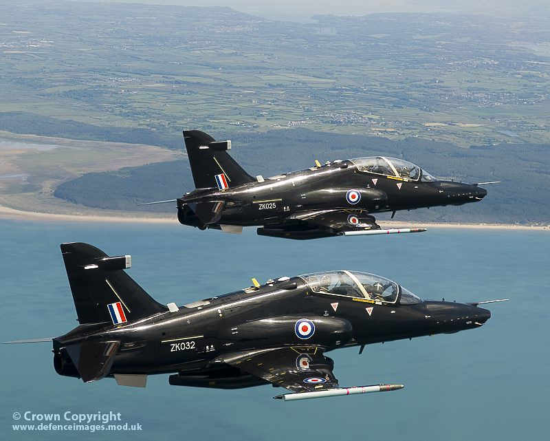 Image shows two fast jet trainng aircraft flying side by side over the coast - probably Anglesey which is where the trainers are based.