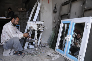 Worker at aluminum shop makes window frames | by World Bank Photo Collection