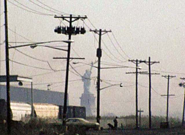 The Statue of Liberty framed by crookedly leaning telephone poles, three train cars, Jersey swamps, a 1970s Chevy and what appears to be a man walking a dog. Caven Point Road. Jersey City. April 1976