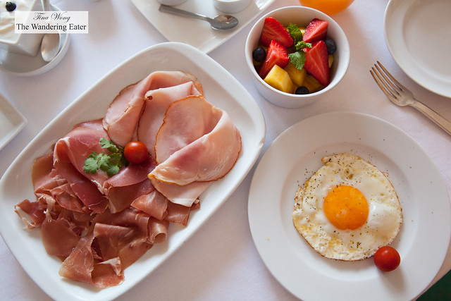 Two different hams, fried egg, bowl of mixed fruit