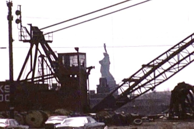 The Statue of Liberty surrounded by rusting cranes, a pile of discarded tires, abandoned cars and a deserted Central Railroad of NJ train yard tower. The view from the end of Warren Street. A frame from my Super8 film