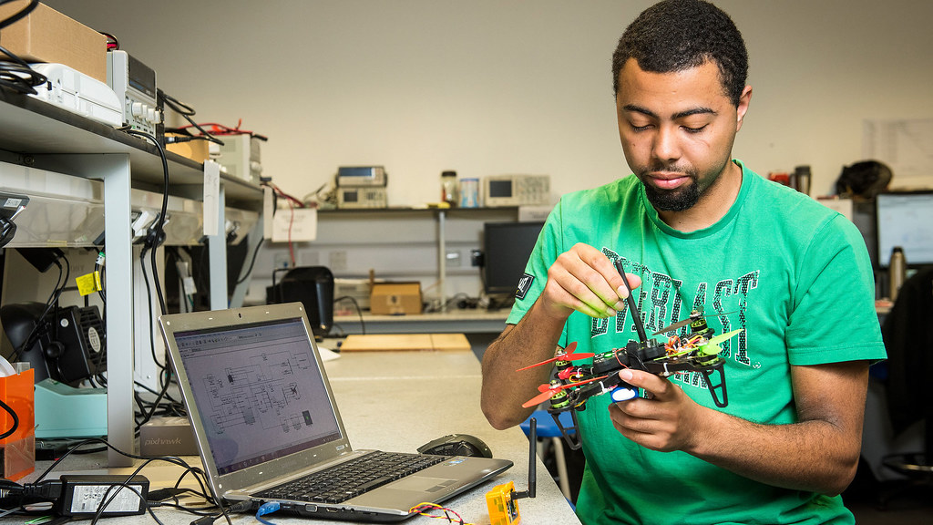 student sits at table in lab holding a drone