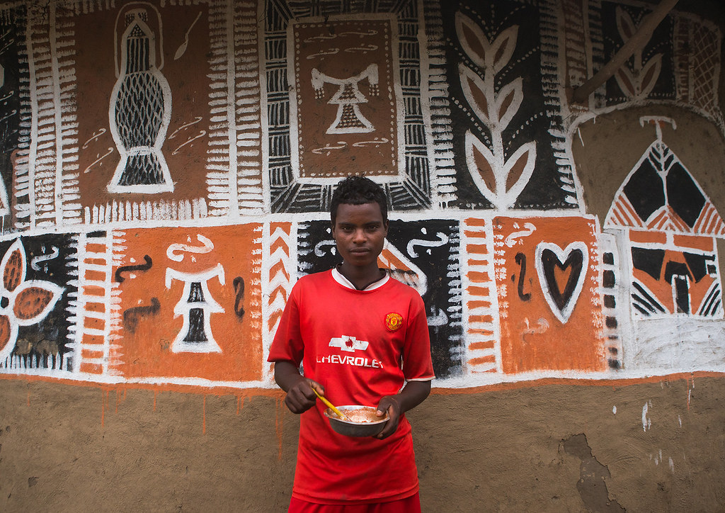 Young man painting the wall of a traditional ethiopian hou