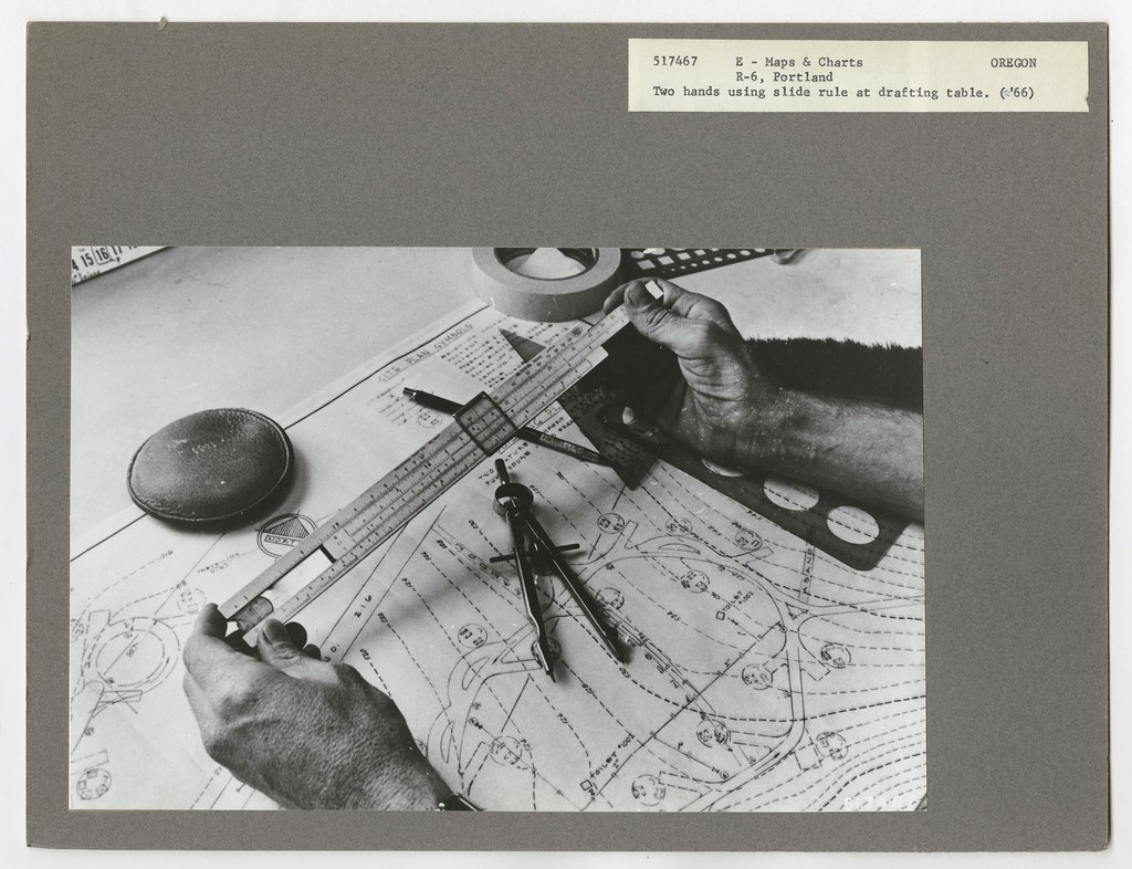 c 1966  Two hands using a slide rule at a drafting table