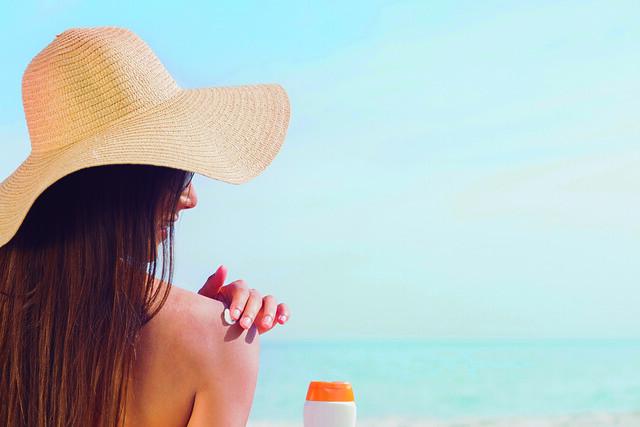 Brunette putting sunscreen on her shoulder