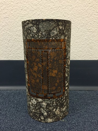 December 12, 2016 - 4:34pm - This is a custom strain gage designed and manufactured by Micro-Measurements for large area strain averaging on asphalt core samples.  There is a grid for measuring hoop strain, one for axial strain, and a shear half-bridge for measuring torsional strain.  All strain gages measure the average strain under the area of their sensing grids, so these large grids correctly average on the non-homogenous asphalt material.