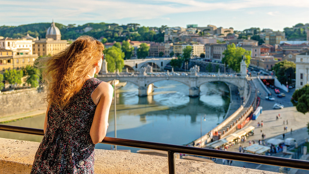 Woman looking at view from bridge in Europe