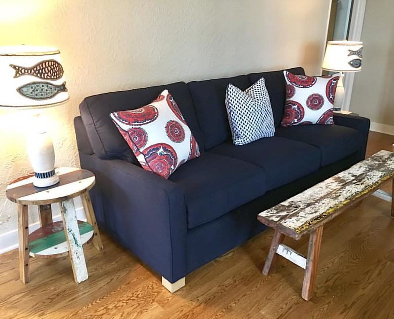 Fun #lakehouse cottage update with a #leeindustries sofa upholstered in #sunbrellafabric paired with one of a kind #reclaimedboatfurniture! #belltowerdesign #lakehouseliving #lakehousedesign #interiordesign #gulllake #coastalliving
