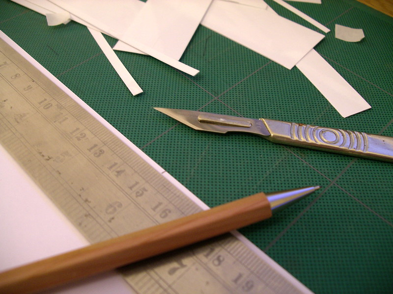 Photo of a scalpel and pencil on a cutting mat