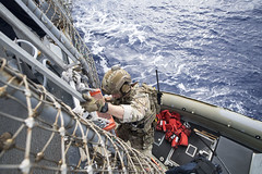 A U.S. Coast Guard Law Enforcement Detachment 103 member boards a rigid hull inflatable boat for an OMSI mission, Feb. 1. (U.S. Navy/MC3 Danny Kelley)