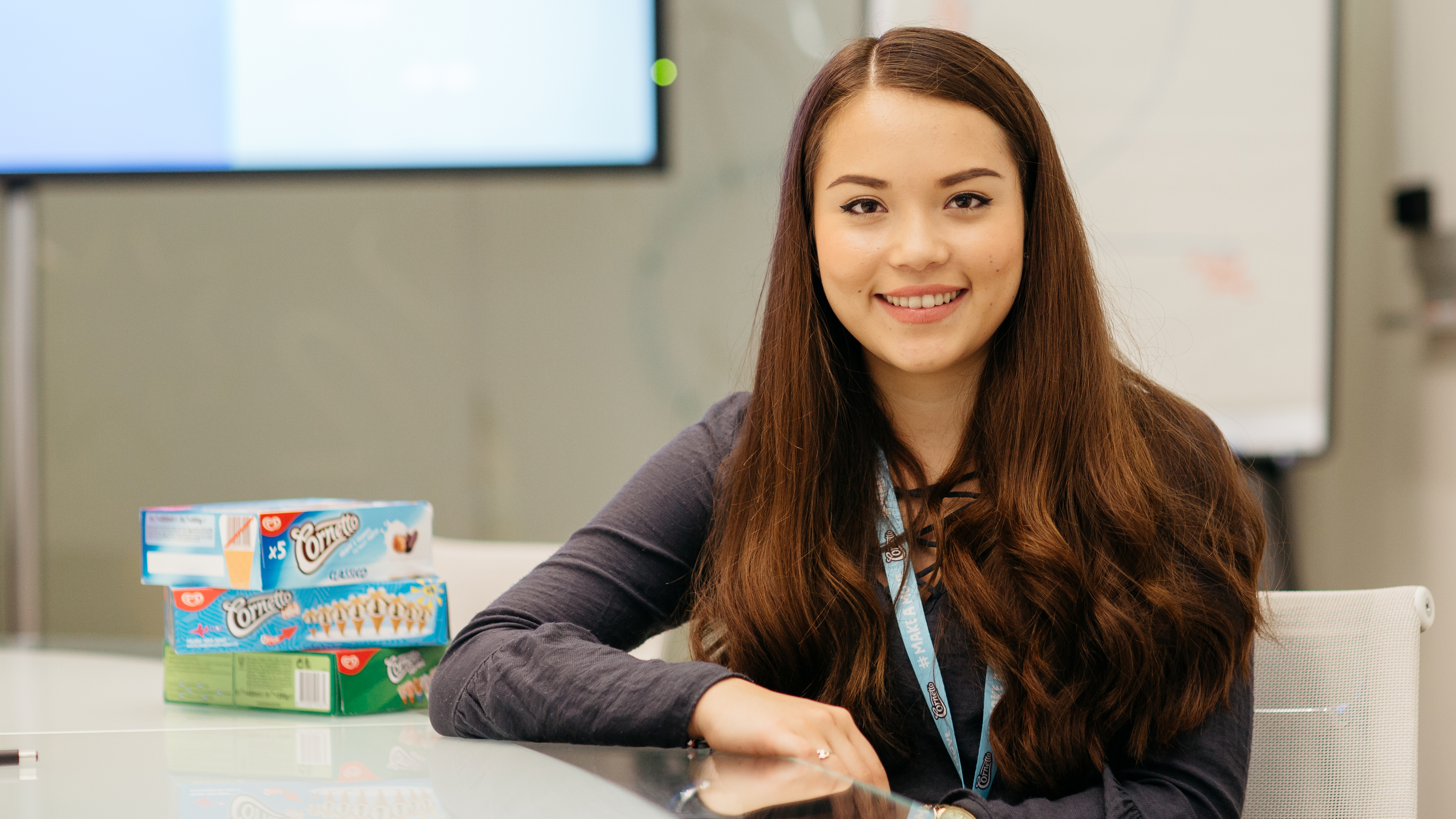 A young woman smiling towards the camera with some boxed food products next to her on a table.
