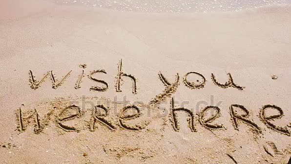 Conceptual wish you were here text handwritten in sand on a beach.