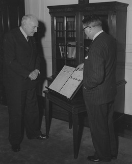 Photograph of Charles Braibant, Director of the Archives of France and President of the International Council on Archives, and Wayne C. Grover, Archivist of the United States, Examining the Original Treaty of Amity and Commerce Signed on February 6,