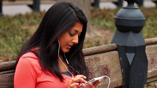 woman-listening-music-park-smartphone-footage-022798689_prevstill