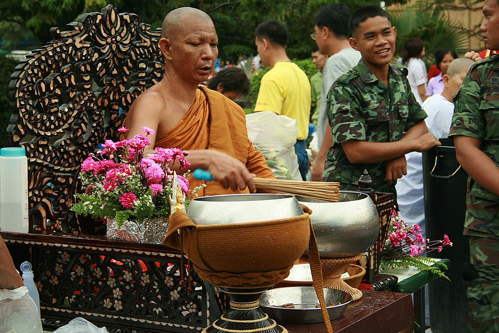 an important monk blessing people (he dips the whisk in water and flings the water at people)